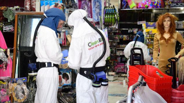 عمال يقومون بتطهير متجر في أور يهودا، بعد أن تبين أن الرجل الذي يعمل في المتجر وعاد من إيطاليا كان مصابًا بفيروس كورونا، 28 فبراير 2020. (Flash90)