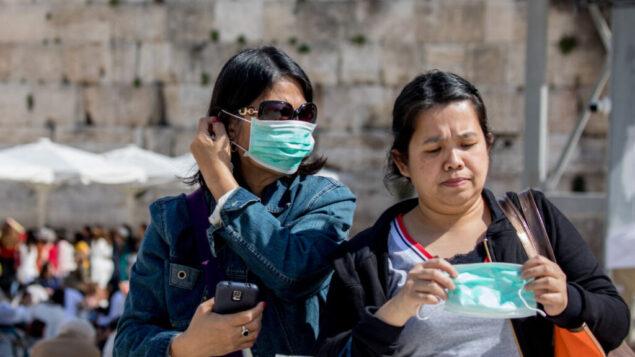 سياح يرتدون أقنعة وجه خوفا من فيروس كورونا خلال جولة في الحائط الغربي في البلدة القديمة في القدس، 05 مارس 2020. (Olivier Fitoussi / Flash90)