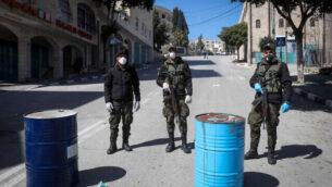 عناصر في قوى الأمن الفلسطينية تضع أقنعة وتغلق مدخل مدينة بيت لحم بالضفة الغربية،  8 مارس، 2020.  (Wisam Hashlamoun/Flash90)