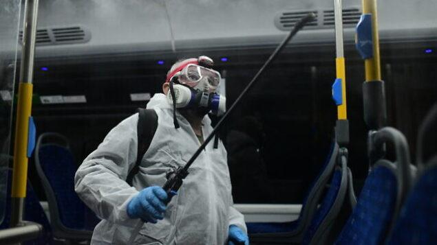 عمال يرتدون بدلات واقية يقومون بتطهير حافلة كإجراء وقائي وسط مخاوف من انتشار فيروس كورونا، في تل أبيب، 9 مارس 2020 (Tomer Neuberg/Flash90)
