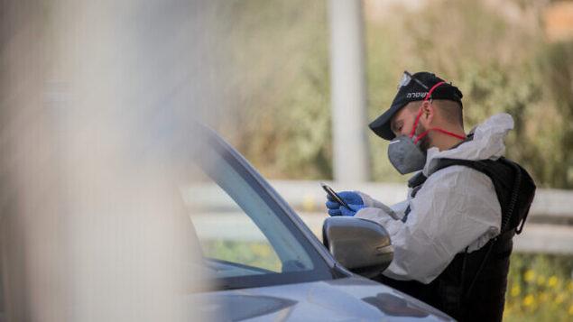 عنصر في شرطة حرس الحدود الإسرائيلية يرتدي معدات واقية وقناع  عند حاجز  'عين ياعيل'، قرب حديقة الحيوان التوراتية في القدس، 11 مارس، 2020.  (Yonatan Sindel/Flash90)