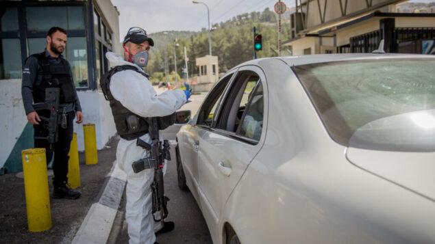عناصر شرطة الحدود الإسرائيلية ترتدي معدات واقية وأقنعة ضد فيروس كورونا، على حاجز عين يائيل، بالقرب من حديقة حيوانات القدس التوراتية، 11 مارس 2020. (Yonatan Sindel / Flash90)
