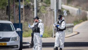 عنصران في شرطة حرس الحدود يرتديان معدات وقائية وأقنعة في حاجز 'عين ياعيل'، بالقرب من حديقة الحيوانات التوراتية، 11 مارس، 2020.  (Yonatan Sindel/Flash90 )