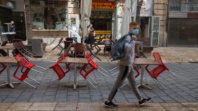 إسرائيلي يضع قناعا وسط المخاوف من فيروس كورونا يسير في وسط مدينة القدس، 15 مارس، 2020.  (Photo by Nati Shohat/Flash90)