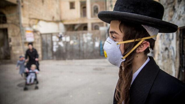 فتى حريدي يضع قناعا في حي مئة شعاريم في القدس، 16 مارس، 2020.   (Yonatan Sindel/Flash90)