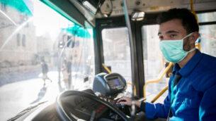 سائق حافلة يضع قناعا وسط المخاوف من انتشار فيروس كورونا في وسط مدينة القدس، 16 مارس، 2020.(Yonatan Sindel/Flash90)