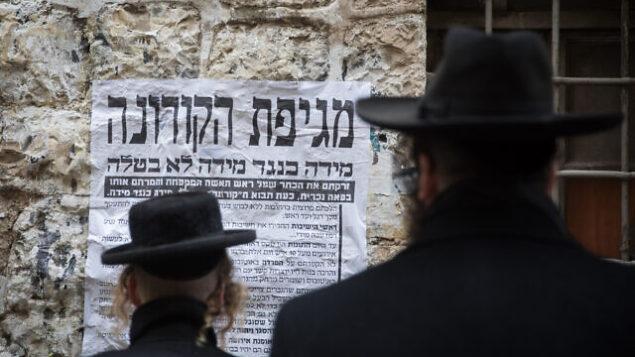 رجال يهود حريديم ينظرون إلى ملصق معلومات حول فيروس كورونا في القدس، 18 مارس، 2020.(Yonatan Sindel/Flash90 )