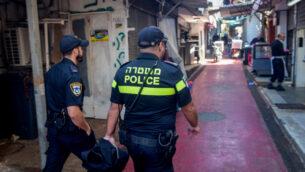 ضباط الشرطة الإسرائيلية يغلقون المتاجر إثر قرار حكومي، في سوق الكرمل في تل أبيب، 22 مارس 2020 (Avshalom Sassoni / Flash90)