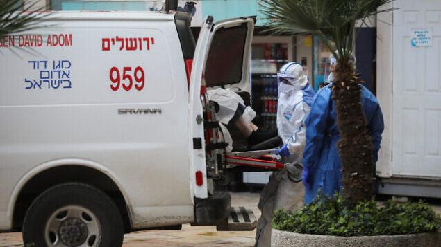 طواقم إسعاف يرتدون زيا واقيا، كإجراء وقائي ضد فيروس كورونا، يقومون بإخلاء سيدة يُشتبه بإصابتها بCOVID-19  في مستشفى هداسا عين كارم، في القدس، 22 مارس، 2020.  (Flash90)