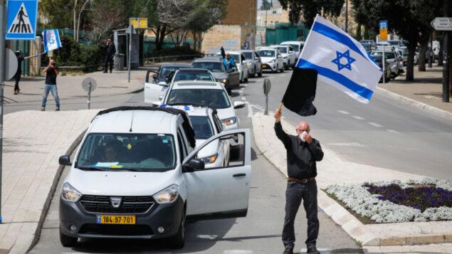 متظاهرون يشاركون في مظاهرة ضد الإجراءات الحكومية التي تم تفسيرها على أنها احتياطات بسبب تفشي فيروس كورونا ولكنهم يرون أنها معادية للديمقراطية، خارج الكنيست في القدس، 23 مارس 2020. (Olivier Fitoussi / Flash90)