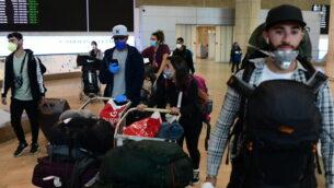 توضيحية: مسافرون إسرائيليون كانوا عالقين في أمريكا الجنوبية يصلون إلى مطار بن غوريون في 23 مارس، 2020، من مدينة ساو باولو البرازيلية، عبر نيويورك.  (Tomer Neuberg/Flash90)