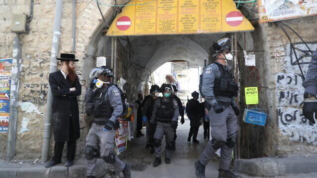 عناصر شرطة إسرائيلية في حي 'مئة شعاريم' الحريدي بالقدس يقومون بإغلاق المحلات التجارية وتفريق التجمعات العامة عقب قرارات الحكومة التي صدرت في محاولة لاحتواء انتشار فيروس كورونا، 24 مارس، 2020. (Yonatan Sindel/Flash90)