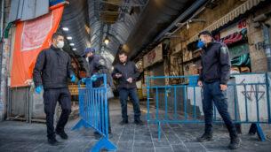 عمال بلدية القدس يغلقون مداخل سوق محانيه يهودا في القدس، 24 مارس 2020. (Yonatan Sindel / Flash90)