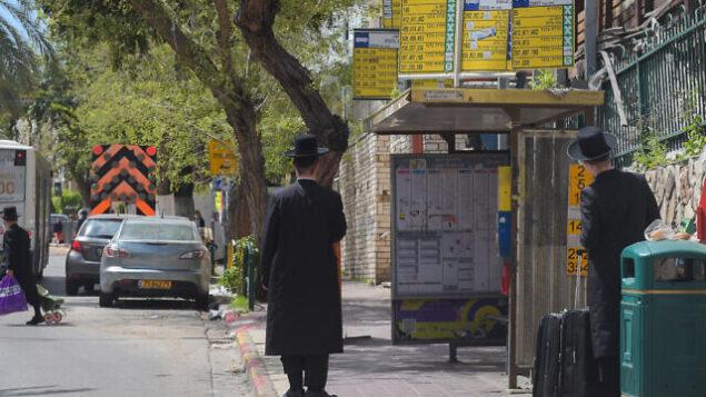 رجال يهود حريديم في انتظار الحافلة في بني براك، 25 مارس، 2020. (Avshalom Sassoni/Flash90)