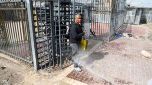 عمال صحة فلسطينيون يقومون بإجراء تعقيم لعمال فلسطينيين عائدين من إسرائيل عند حاجز في ترقوميا، ٫ 25 مارس، 2020. (Wisam Hashlamoun/Flash90)