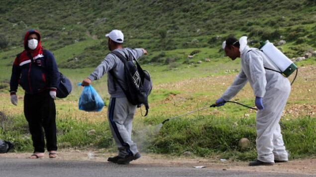 عمال صحة فلسطينيون يقومون بإجراء تعقيم لعمال فلسطينيين عند عودتهم من إسرائيل عند حاجز في ترقميا، 25 مارس، 2020.  (Wisam Hashlamoun/Flash90)