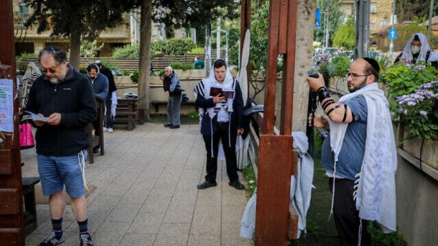 رجال يهود يصلون خارج كنيس في حي نحالوت بالقدس، 25 مارس، 2020.  (Yossi Zamir/Flash90)