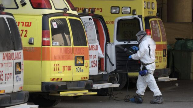 طواقم طبية تطهر سيارة إسعاف في فندق دان بانوراما في تل أبيب، الذي تم تحويله إلى منشأة للحجر الصحي ضد فيروس كورونا، 26 مارس 2020. (Gili Yaari / Flash90)