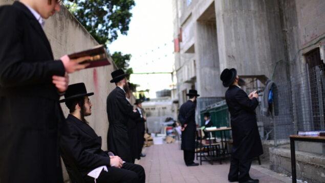رجال يهود متشددون يصلون خارج مدرسة دينية مغلقة، في بلدة بني براك، 26 مارس 2020. (Tomer Neuberg / Flash90)