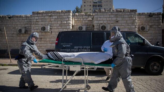 توضيحية: قائمان على الدفن يرتديان زيا واقيا ويحملان جثة مريض توفي جراء وباء كورونا (COVID-19) في دار دفن الموتى 'شمغار' في القدس، 29 مارس، 2020. (Yonatan Sindel/Flash90)