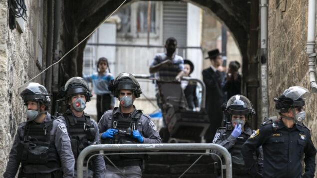 عناصر شرطة اسرائيليون يدخلون حي ميا شعاريم في القدس لإنفاذ قيود الحكومة من اجل مكافحة فيروس كورونا، 30 مارس 2020 (Olivier Fitoussi / Flash90)