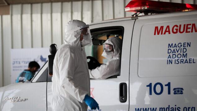 عاملان في نجمة داوود الحمراء يرتدون زيا واقيا، كإجراء وقائي ضد فيروس كورونا، يقمون بنقل رجل يُشتبه بإصابته بالفيروس في مستشفى شعاري تسيدك بالقدس، 30 مارس، 2020. (Yossi Zamir/Flash90)