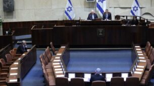 قاعة الكنيست فارغة تقريبًا، بسبب القيود ضد انتشار فيروس كورونا، أثناء أداء اليمين الدستورية للكنيست الثالثة والعشرين، 16 مارس ، 2020. (Gideon Sharon / Knesset Spokesperson)