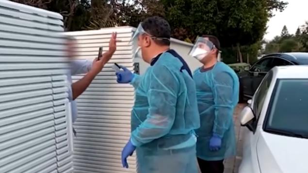 إسرائيلي في حجر صحي بعد عودته من تايلاند يرفع الأصبع الوسطى في وجه مفتشتين من وزارة الصحة خلال زيارة قاموا بها إلى منزاله في 23 فبراير، 2020.  (Screen capture/YouTube)