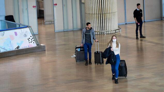 مسافرون يضعون الأقنعة وسط المخاوف من فيروس كورونا في مطار بن غوريون الدولي قرب تل أبيب،  10 مارس، 2020. (Avshalom Sassoni/Flash90)