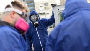 عمال يرتدون ملابس واقية يقومون بتطهير ملعب عام في بات يام في إطار  إجراءات لمنع انتشار فيروس كورونا، 18 مارس، 2020.   (Tomer Neuberg/Flash90)