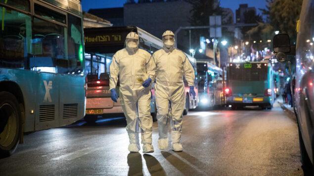 عاملون في المجال الطبي يرتدون بدلات واقية كإجراء وقائي ضد فيروس كورونا، عند وصولهم لاختبار مريض يعاني من أعراض، القدس، 16 مارس 2020. (Yonatan Sindel / Flash90)