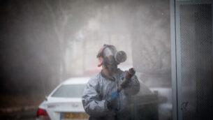 رجل إطفاء إسرائيلي يرتدي زيا واقيا ويقوم بإجراء تطهير لحافلة في بلدة كريات يعاريم الحريدية بعد أن تم تشخيص إصابة 17 شخصا من سكانها بفيروس كورونا، 18  مارس، 2020.(Yonatan Sindel/Flash90)