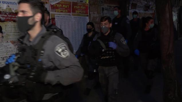 عناصر شرطة اسرائيليون يدخلون حي ميا شعاريم في القدس لإنفاذ قيود الحكومة من اجل مكافحة فيروس كورونا، 30 مارس 2020. (Screen capture: Israel Police)