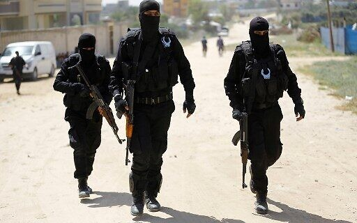 صورة توضيحية: رجال شرطة حماس خلال مداهمة في النصيرات، جنوب مدينة غزة، 22 مارس 2018. (AFP Photo / Mohammed Abed)