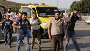 صورة تم التقاطها في الجانب الإسرائيلي من حاجز ترقوميا بالقرب من مدينة كريات غات جنوبي البلاد يظهر فيها عمال فلسطينيون عند دخولهم إلى إسرائيل للوصول إلى أعمالهم، 14 نوفمبر، 2019. (HAZEM BADER / AFP)