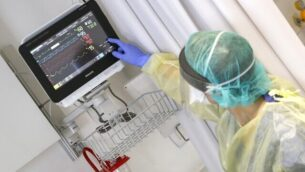 مديرة خدمة الأوبئة، دكتور كارينا غليك، تقوم بفحص جهاز مراقبة أحد المرضى وترتدي زيا واقيا، خلال خلال عرض صحفي حول خدمات المستشفى للمرضى  المصابين بفيروس كورونا في مستشفى سمسون أسوتا أشدود الجامعي، 16  مارس،  2020، في مدينة أشدود جنوبي إسرائيل. (Jack Guez/AFP)