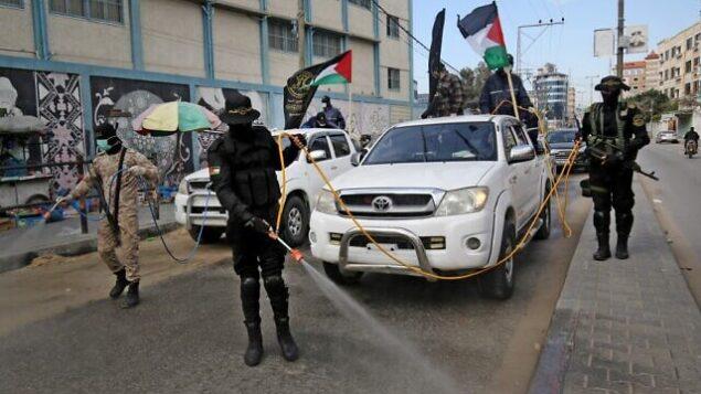 عناصر في الجناح العسكري لحركة الجهاد الإسلامي الفلسطينينة، سرايا القدس، يقومون بإجراءات تعقيم في شوارع مدينة رفح جنوبي قطاع غزة، 26 مارس، 2020. (Said Khatib/AFP)