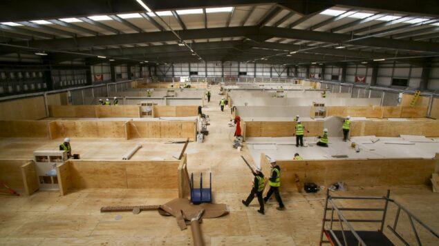 عمال يبنون مساحات لمئات الأسرة في مركز تدريب داخلي في بارسي سكارليتس في جنوب ويلز، 30 مارس 2020 (