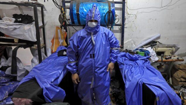 عمال فلسطينيون يصنعون ملابس واقية في مصنع بمدينة غزة، 30 مارس 2020 (MAHMUD HAMS / AFP)