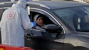 مسعف نجمة داود الحمراء يختبر امرأة لفيروس كورونا في موقع اختبار 'درايف ثرو' في مدينة طمرة الشمالية، 31 مارس 2020 (Ahmad Gharabli / AFP)