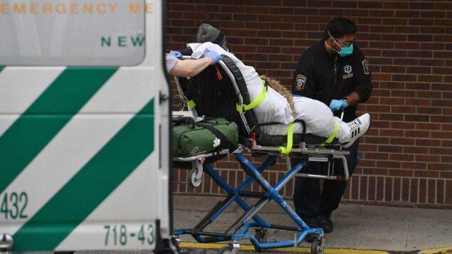 مسعفون يدفعون مريض إلى غرفة الطوارئ في مستشفى بروكلين في نيويورك، 31 مارس 2020. (Angela Weiss/AFP)