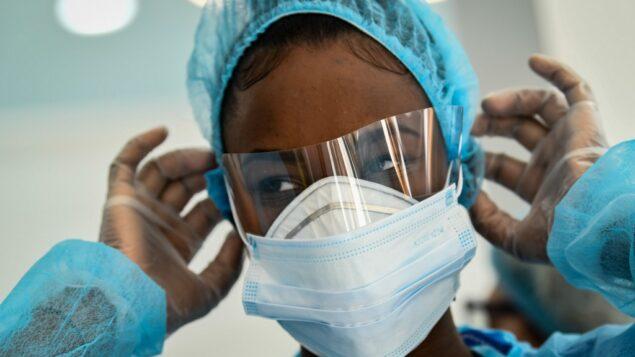 صورة توضيحية: موظفة طبية تعدل قناع الوجه الواقي لها في مركز طبي في باريس، 1 أبريل 2020 (BERTRAND GUAY / AFP)