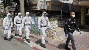 عناصر في الشرطة الإسرائيلية في زي واق يصلون إلى معهد ديني في مدينة بني براك الإسرائيلي في 2 أبريل، 2020، لضمان تطبيق إجراءات التباعد الاجتماعي التي فرضتها الحكومة الإسرائيلية في محاولة للحد من انتشار فيروس كورونا.   (JACK GUEZ / AFP)