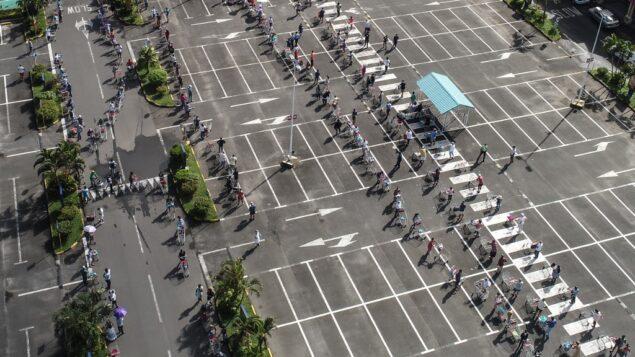 صورة جوية تظهر أشخاص ينتظرون أثناء الحفاظ على التباعد الاجتماعي في موقف للسيارات قبل دخول سوبر ماركت في موريشيوس، 2 أبريل 2020 (L'EXPRESS MAURICE / AFP)