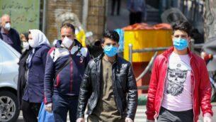إيرانيون يرتدون أقنعة واقية ضد فيروس كورونا أثناء سيرهم في أحد شوارع العاصمة طهران، 5 أبريل 2020 (ATTA KENARE / AFP)