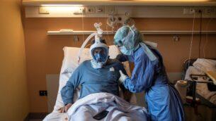 ممرضة تساعد مريضا يعاني من COVID-19 ويرتدي قناع للغطس في قسم كورونا في مستشفى ماريا بيا في تورينو، إيطاليا، 7 أبريل 2020 (MARCO BERTORELLO / AFP)