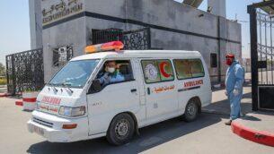 سيارة إسعاف تمر امام احد عناصر قوات الأمن التابعة لحركة حماس، التي تحكم قطاع غزة، في معبر رفح الحدودي مع مصر، 13 أبريل 2020. (Said Khatib / AFP)