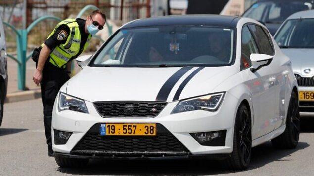 شرطي إسرائيل يقوم بالتحقق من التزام المركبات بعدم خرق الإغلاق المؤقت الذي فُرض على قرية دير الأسد في 16 أبريل، 2020، خلال أزمة جائحة فيروس كورونا المستجد.  (Ahmad GHARABLI / AFP)