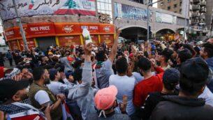 مئات اللبنانيين يتظاهرون في مدينة طرابلس الشمالية على الرغم من حظر التجول بسبب فيروس كورونا في البلاد، بمناسبة مرور ستة أشهر منذ أن هزت البلاد مسيرات حاشدة ضد الفساد الحكومي والصعوبات الاقتصادية، 17 أبريل 2020 (Ibrahim CHALHOUB / AFP)