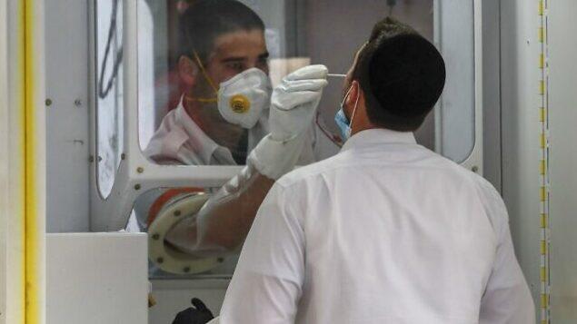 مسعف في نجمة داوود الحمراء يجري فحص فيروس كورونا لرجل حريدي في محطة فحوصات متنقلة، في حي غئولا بالقدس، 20 أبريل، 2020.  (Ahmad Gharabli/AFP)